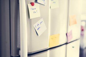 Closeup of reminder paper note on fridge door