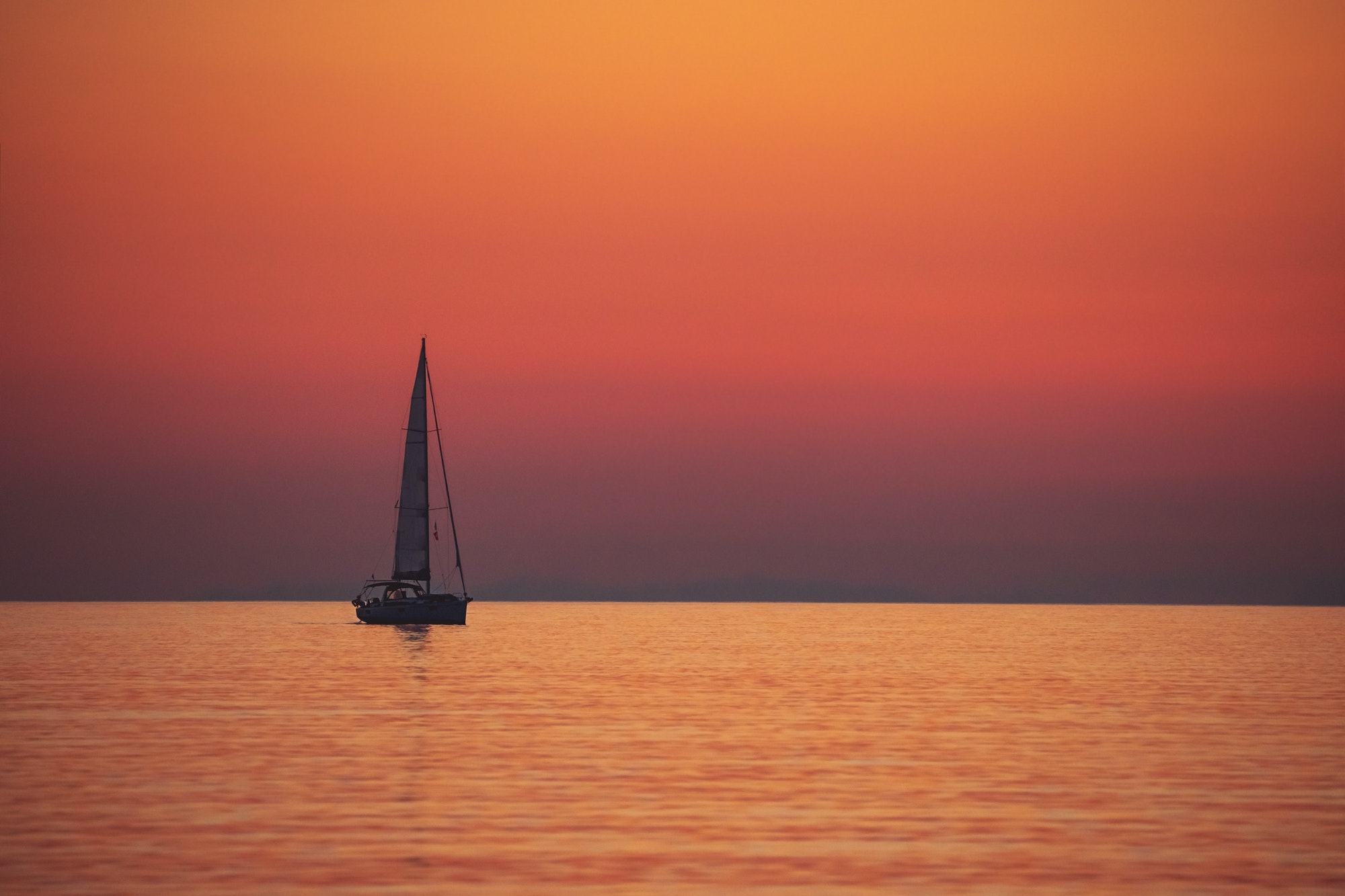 Sail boat over sunset